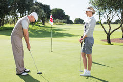 Pares Golfing en el putting green en el décimo octavo agujero Imagenes de archivo