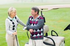 Pares golfing felices con el cochecillo del golf detrás Fotografía de archivo libre de regalías