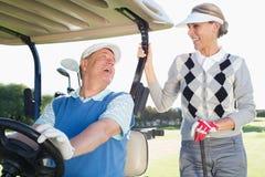 Pares golfing felices que se establecen para el día en el cochecillo fotografía de archivo
