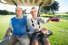 Pares golfing felices que se sientan en cochecillo del golf fotos de archivo libres de regalías