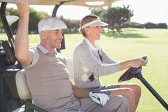 Pares golfing felices que sonríen en su cochecillo imágenes de archivo libres de regalías