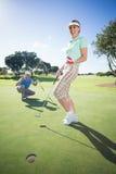 Pares Golfing que animan en el putting green Foto de archivo libre de regalías