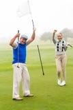 Pares Golfing que animan en el putting green Foto de archivo