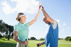 Pares Golfing que fiving altamente no campo de golfe imagem de stock royalty free