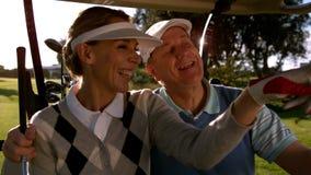 Pares Golfing que sientan la mirada con errores alrededor del curso almacen de video