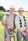 Pares Golfing que sonríen en la cámara en el putting green Fotos de archivo