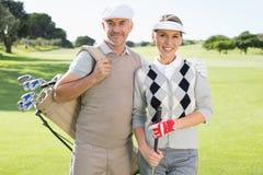 Pares Golfing que sonríen en la cámara en el putting green Imagenes de archivo