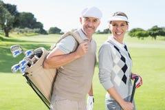 Pares Golfing que sonríen en la cámara en el putting green Foto de archivo libre de regalías