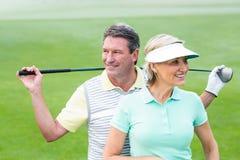 Pares Golfing que sonríen y que detienen a los clubs Imagen de archivo libre de regalías