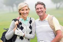 Pares Golfing que sonríen y que detienen a los clubs Fotos de archivo