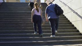 Pares gordos que caminan junto en las escaleras, problemas del exceso de peso entre gente joven almacen de metraje de vídeo