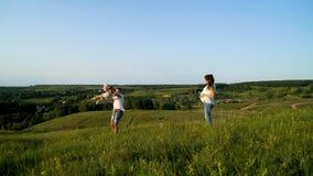 Pares grávidos com a filha da criança que anda nos campos verdes que têm o tempo de lazer foto de stock
