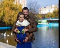 Pares grávidos de sorriso com sapatinhos de lã do bebê mim foto de stock