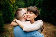 Pares grávidos felizes e dos jovens que abraçam na natureza Imagem de Stock Royalty Free