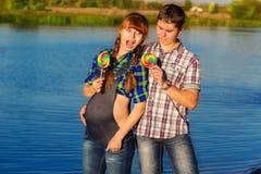 Pares grávidos felizes e dos jovens que têm o divertimento na praia verão Imagens de Stock