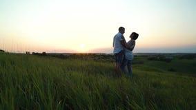 Pares grávidos felizes novos românticos que abraçam na natureza no por do sol vídeos de arquivo