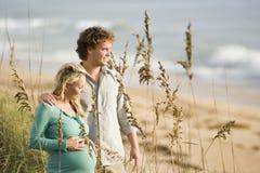 Pares grávidos felizes que estão junto na praia fotografia de stock