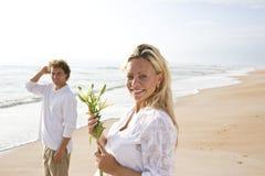 Pares grávidos na praia que prende a flor branca fotos de stock royalty free