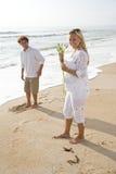 Pares grávidos na praia que prende a flor branca foto de stock royalty free