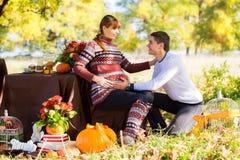Pares grávidos novos bonitos que têm o piquenique no parque do outono Ha Imagem de Stock