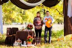 Pares grávidos novos bonitos que têm o piquenique no parque do outono Ha Imagem de Stock Royalty Free