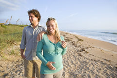 Pares grávidos novos felizes que estão na praia imagem de stock royalty free