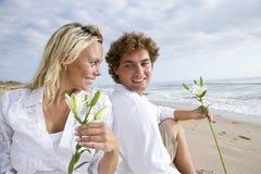 Pares grávidos novos felizes que relaxam na praia imagem de stock royalty free