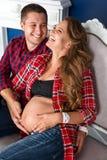 Pares grávidos bonitos que relaxam no sofá em casa junto Família, homem feliz e mulher esperando uma criança Fotografia de Stock Royalty Free