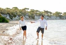 Pares hermosos atractivos en el amor que camina en la playa en vacaciones de verano románticas Foto de archivo libre de regalías