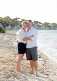 Pares hermosos atractivos en el amor que camina en la playa en vacaciones de verano románticas Fotos de archivo