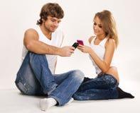 Pares hermosos con los teléfonos móviles Fotografía de archivo