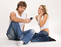 Pares hermosos con los teléfonos móviles Imagen de archivo