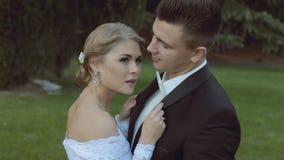 Pares hermosos de la boda en hierba verde cerca del metrajes