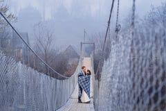 Pares hermosos de la boda que abrazan en el puente en montañas honeymoon fotos de archivo libres de regalías