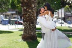 Pares hermosos de la boda que abrazan en parque público en Grecia, mirando uno a, en amor Amor en concepto del aire imagen de archivo libre de regalías