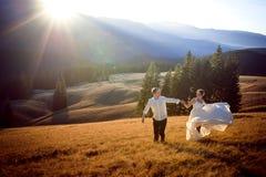 Pares hermosos de la boda que funcionan con y que se divierten en el campo rodeado por las montañas Fotos de archivo
