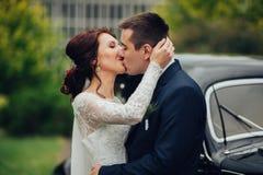 Pares hermosos de la boda que presentan cerca del coche retro espléndido Fotos de archivo