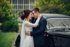 Pares hermosos de la boda que presentan cerca del coche retro espléndido Foto de archivo