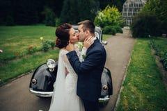 Pares hermosos de la boda que presentan cerca del coche retro espléndido Imagen de archivo