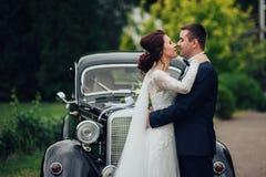Pares hermosos de la boda que presentan cerca del coche retro espléndido Foto de archivo libre de regalías