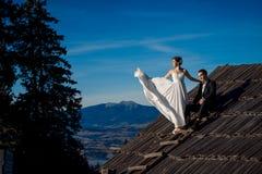 Pares hermosos de la boda que presentan en el top del tejado Fondo asombroso del paisaje de la montaña Fotografía de archivo