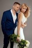 Pares hermosos de la boda que presentan en estudio Fotografía de archivo