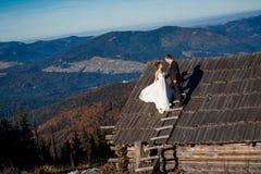 Pares hermosos de la boda que se colocan en el tejado de la casa de campo Fondo asombroso del paisaje de la montaña honeymoon Fotografía de archivo libre de regalías