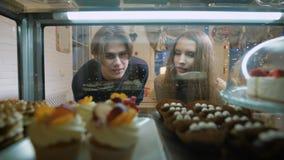Pares hermosos de la gente joven en una tienda de chucherías La muchacha y el individuo la primera fecha, tienen sensaciones romá metrajes