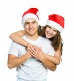 Pares hermosos de la Navidad en los sombreros de Santa Fotos de archivo