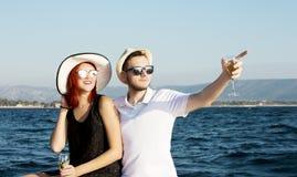 Pares hermosos de los amantes que navegan en un barco Dos modelos de moda que presentan en un barco de navegación en la puesta de Foto de archivo