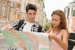Pares hermosos de los turistas que sostienen un mapa adentro Foto de archivo libre de regalías