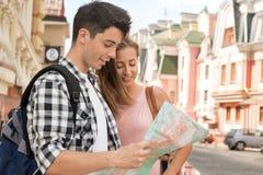 Pares hermosos de los turistas que sostienen un mapa adentro Fotos de archivo libres de regalías