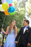 Pares hermosos del baile de fin de curso que caminan con los globos afuera Fotos de archivo libres de regalías