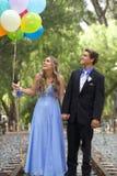 Pares hermosos del baile de fin de curso que caminan con los globos afuera Foto de archivo libre de regalías
